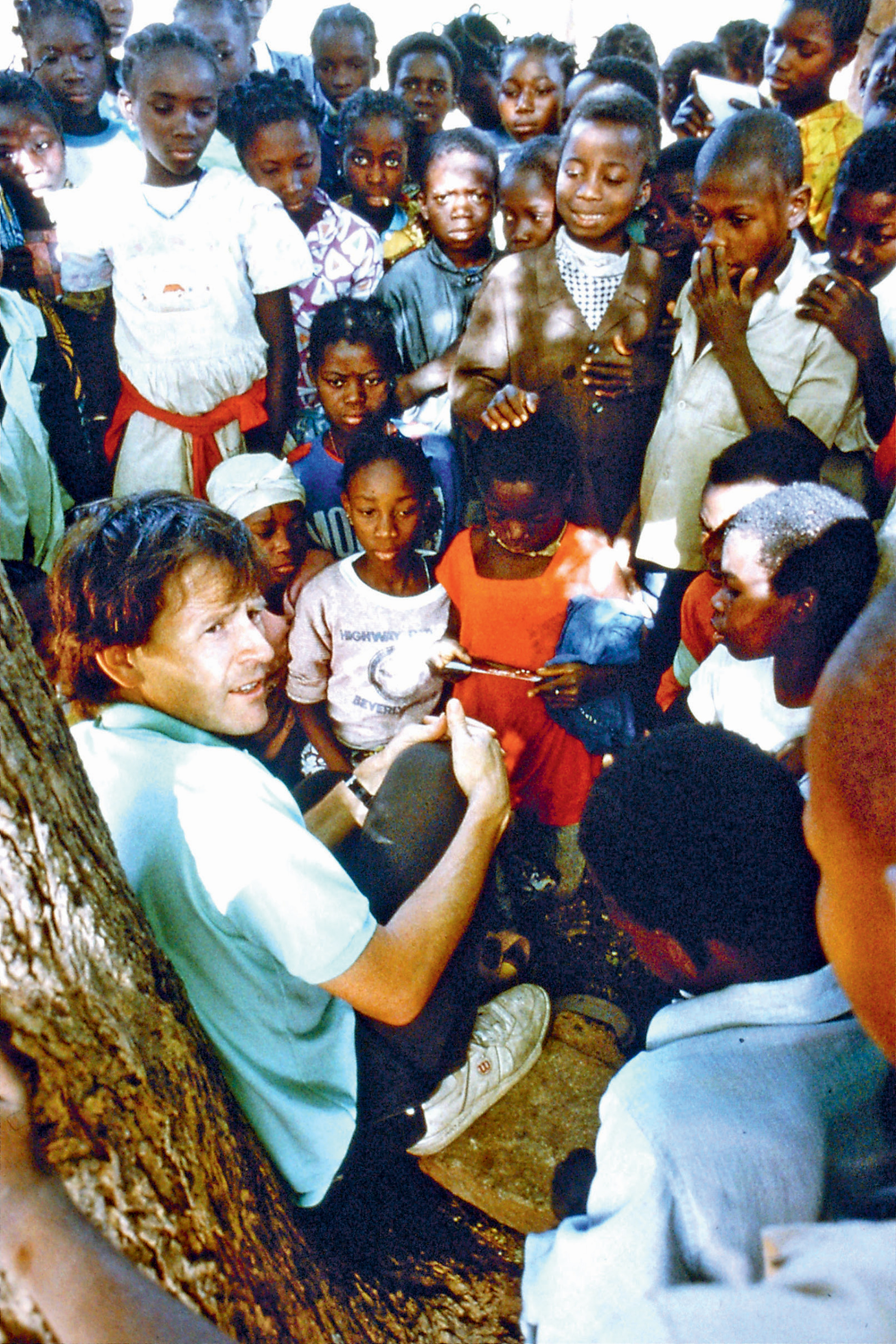Lesson under a tree. Showing photographs and talking about the differences between Britain and Burkina Faso to a class of schoolchildren in 1995.
