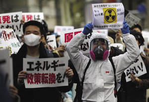 Protesters at an anti-nuclear rally in Tokyo, 27 March 2011. The signs read: 'Change energy policy' and 'Do not sprinkle radioactive material'. jeanbaptisteparis under a CC Licence