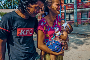 The parents of one-year-old Thin Thawdaw Tun carry their injured daughter, who received treatment from volunteer medics. A rubber bullet fired by the security forces hit her in the eye, while she was inside the family home.Photo: Panos Pictures