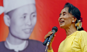 Aung San Suu Kyi on the campaign trail in 2015, standing in front of a poster of her father Aung San, independence hero and founder of Myanmar's armed forces.Photo: Soe Zeya Tun/Reuters
