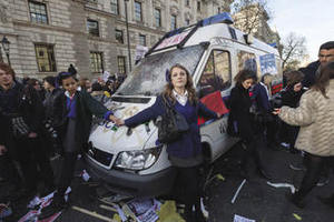 Schoolgirls attempt to prevent further damage to a police van that has been abandoned in the midst of student protests, London, November 2010.Peter Marshall