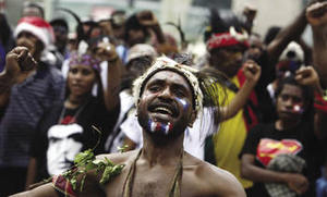 'We will be free!' A Papuan in traditional dress demonstrates against the Indonesian occupation.