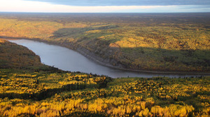 The Athabasca River winds peacefully through the boreal forest.