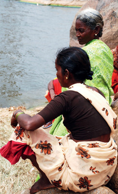 Two women sit patiently by the Kishkindha River in southern India, waiting for the coracle (a round boat) to ferry them to the other bank for work.